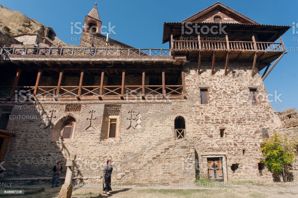People walking past stone wall the 6th century David Gareji monastery with balcony and towers, Georgia stock photo