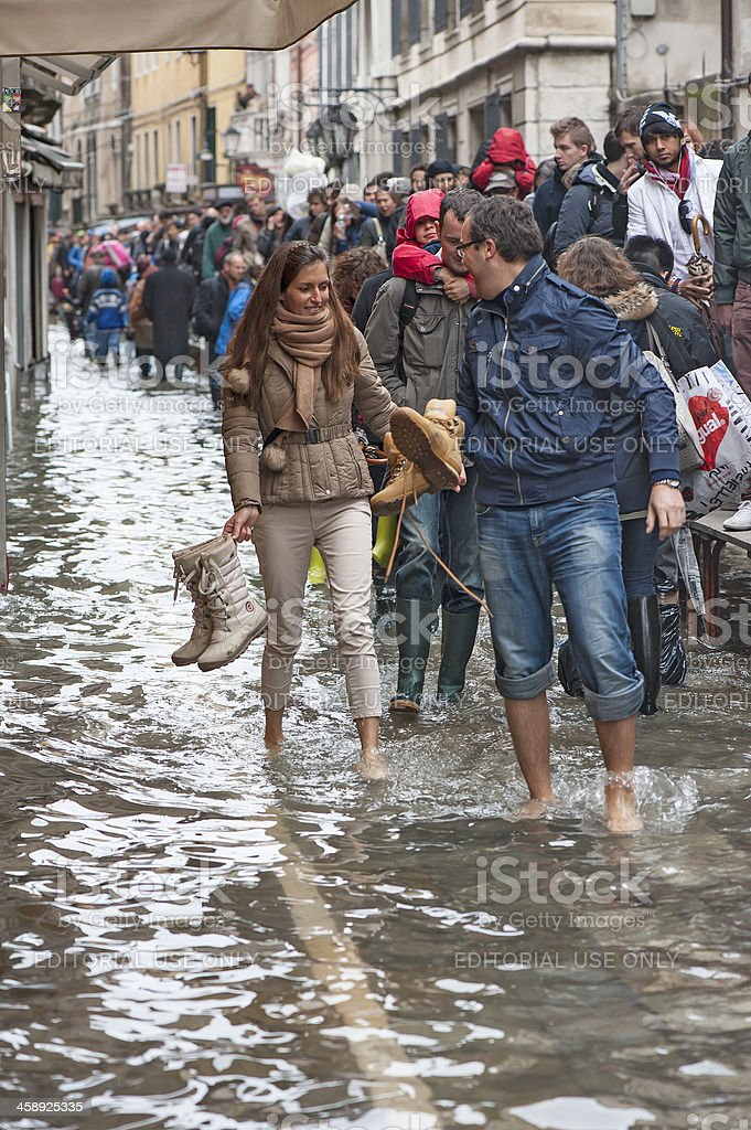 'People walking through a flooded streed in Venice, Italy' stock photo