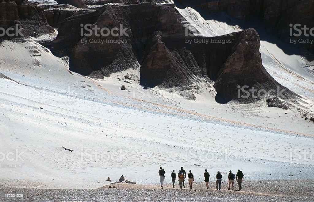 People walking through desert. stock photo
