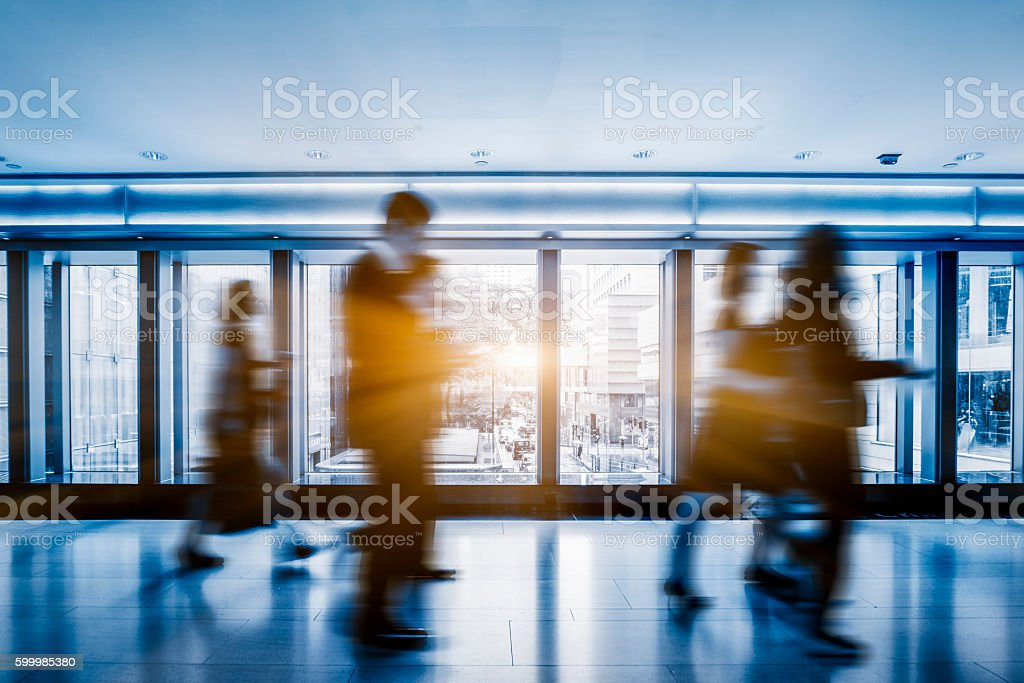 people walking through footbridge in the business area stock photo