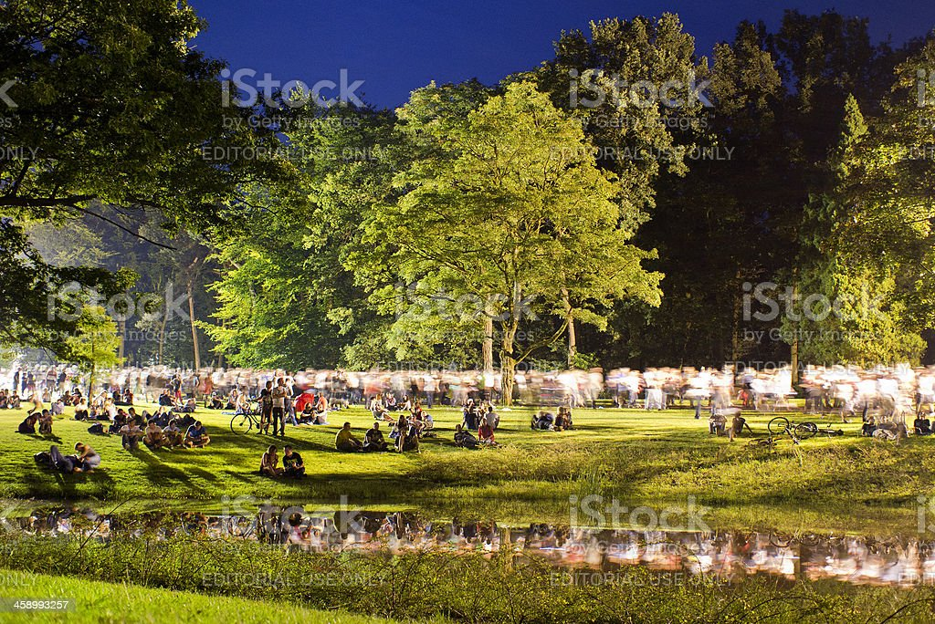 people walking through park after concert at night stock photo
