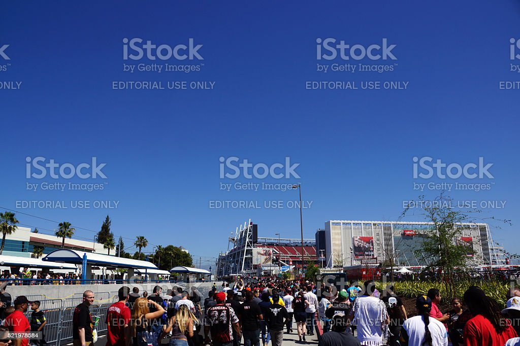 People walking through parking lot to arena for event stock photo