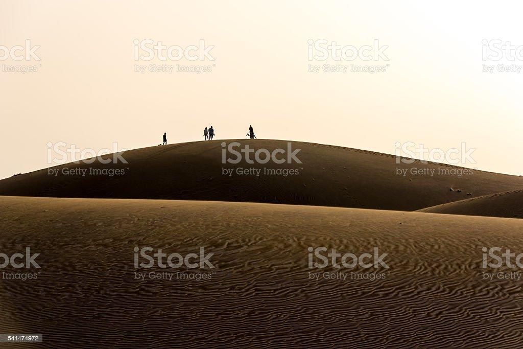 People walking through the desert stock photo