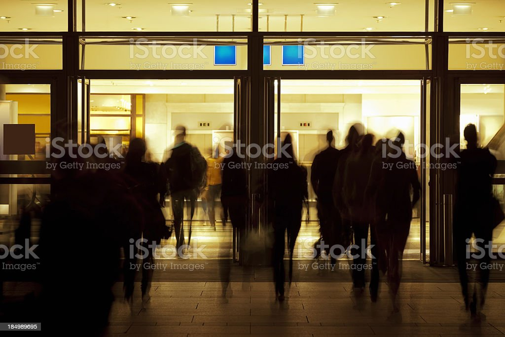 People Walking Toward Illuminated Entrance stock photo