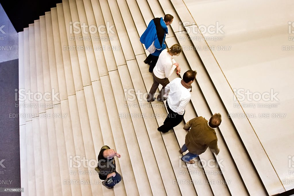 People walking up wide staircase at public building royalty-free stock photo