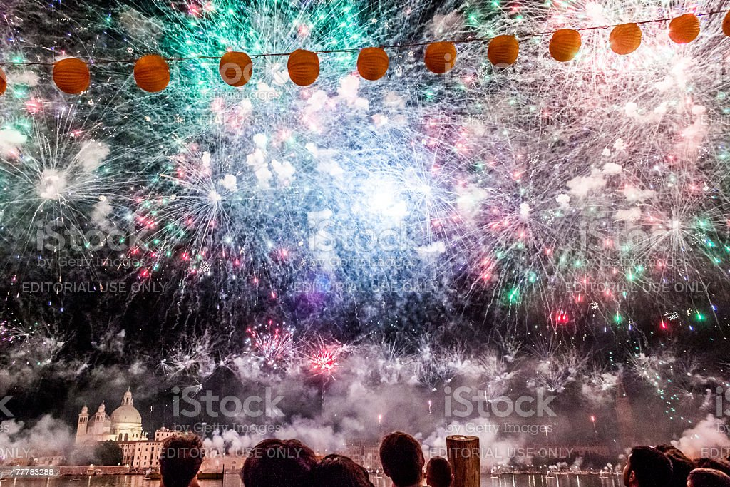People watch a colourful firework display over Venice, Italy for the...