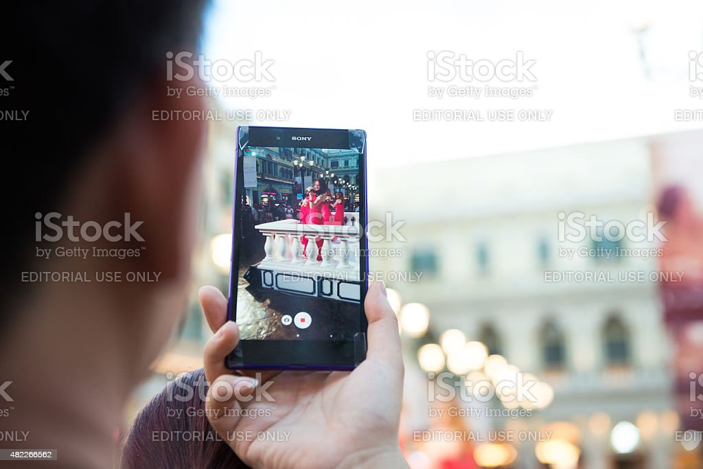 People watching a live show taking photos and videos horizontal stock photo