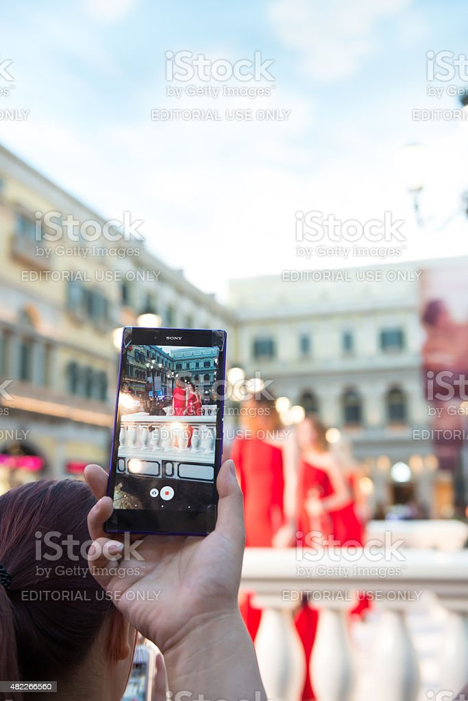People watching a live show taking photos and videos vertical stock photo