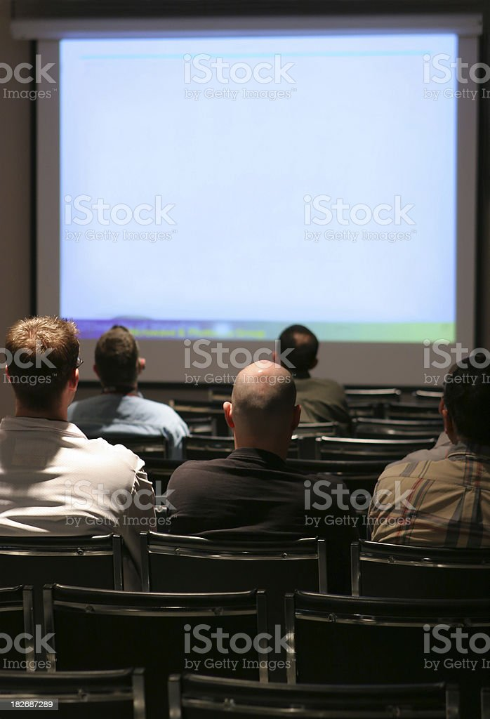 People watching a presentation on a large screen royalty-free stock photo