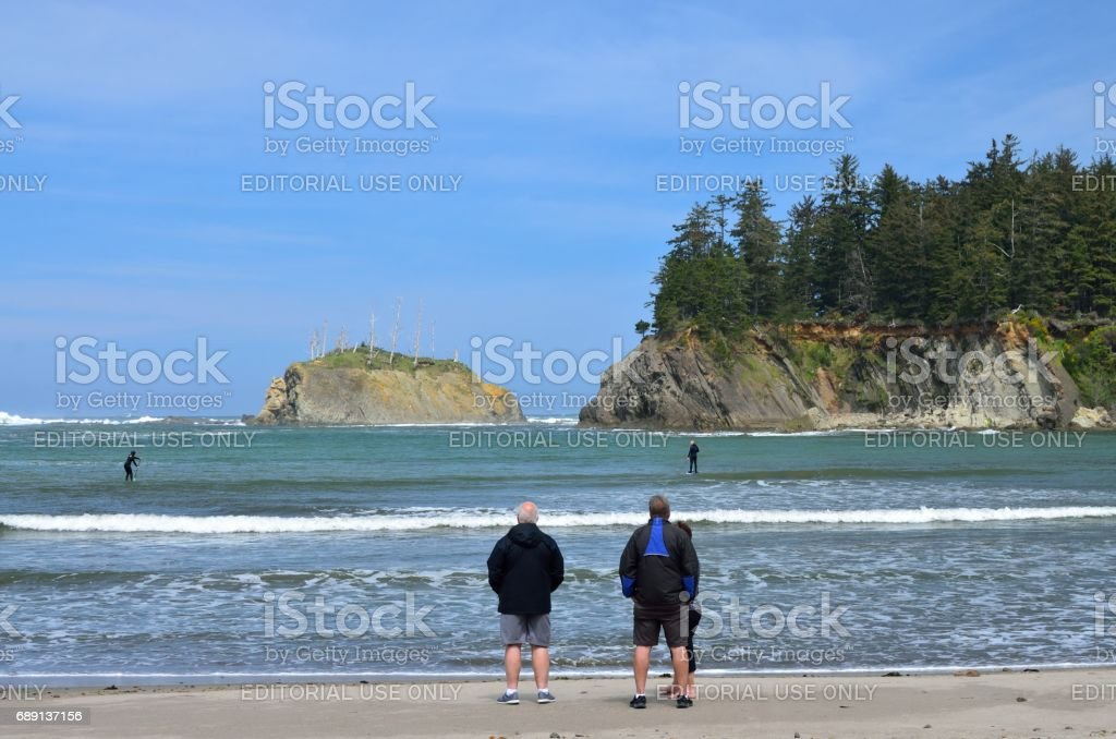 People Watching Paddle Boarders Surfing In Sunset Bay State Park, Oregon stock photo