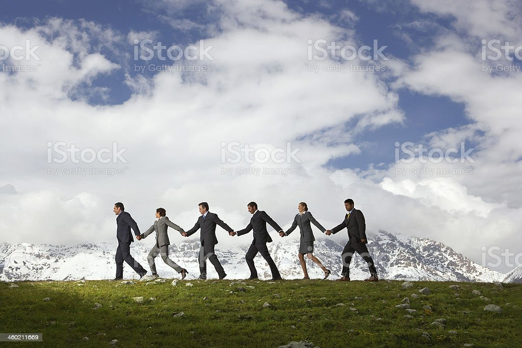 People wearing business clothes holding hands in a valley stock photo