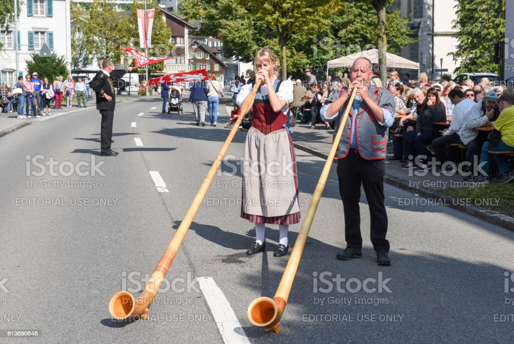 People wearing traditional clothes and playing the alphorn at En stock photo
