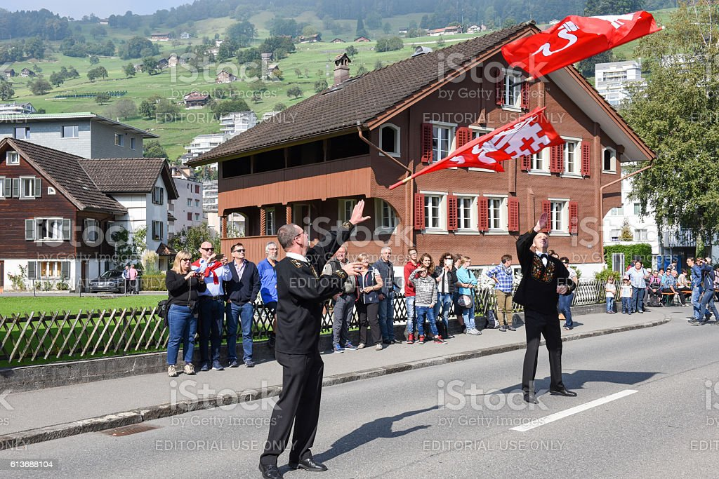 People wearing traditional clothes and waving flags at Ennetbuer stock photo