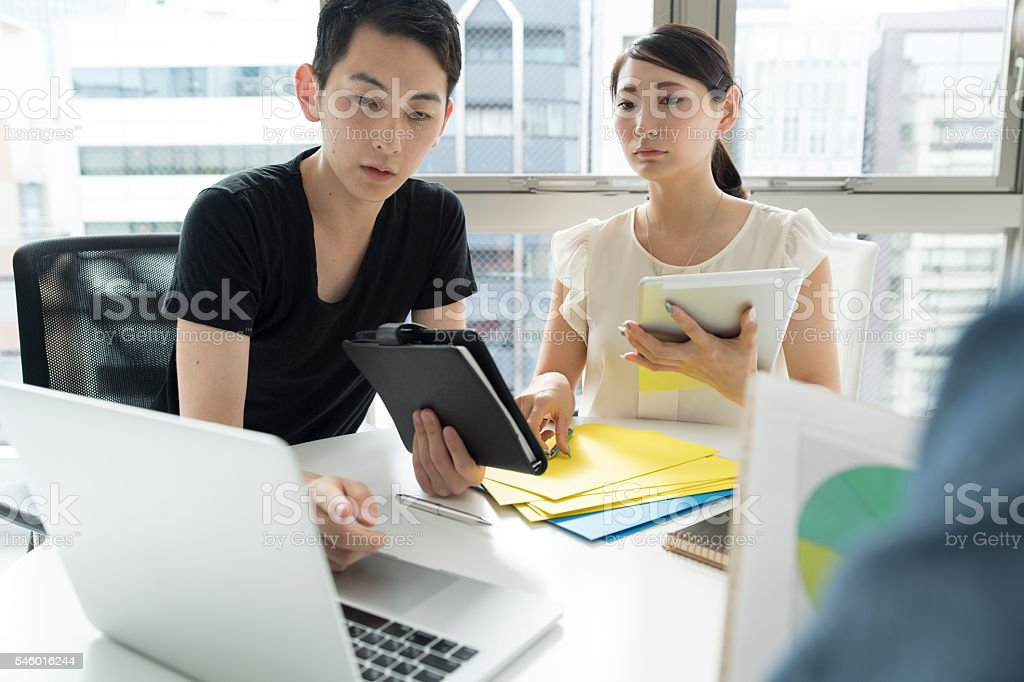 People who have a meeting while showing the laptop documents stock photo