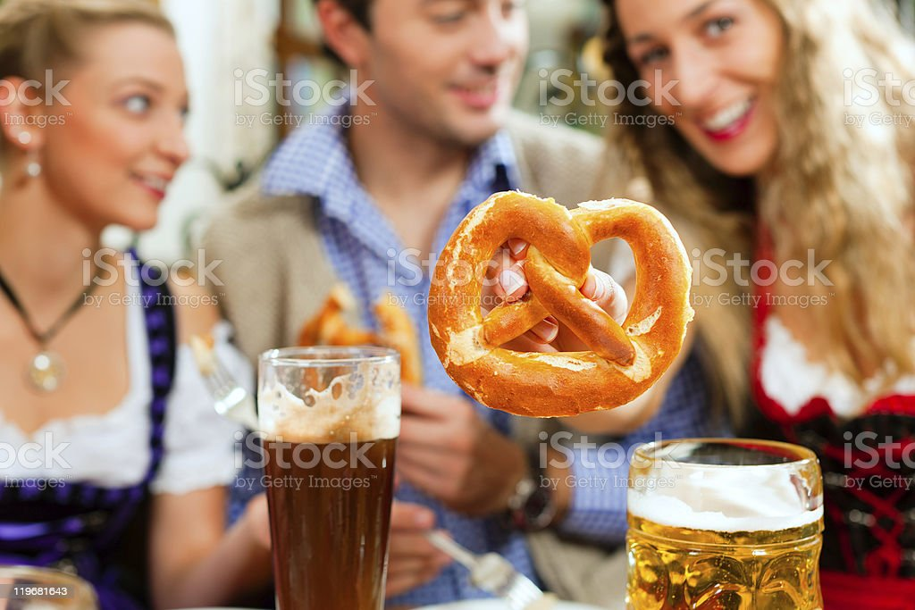 People with beer and pretzel in Bavarian pub royalty-free stock photo