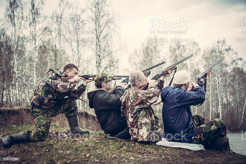 people with guns aimed and prepared to make shot stock photo