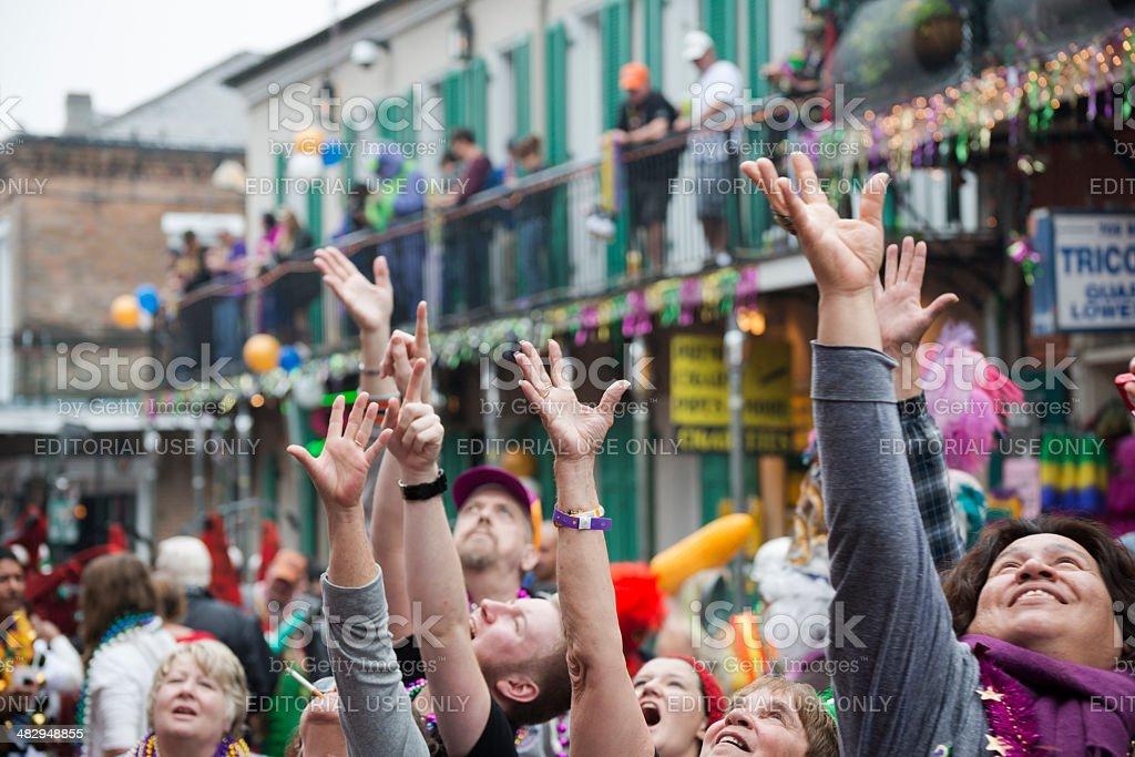 People with hands raised celebrating Mardi Gras on Bourbon Street stock photo