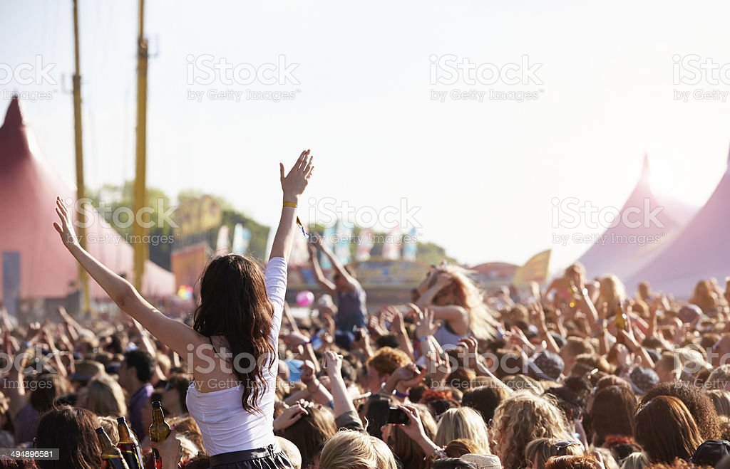 People with their arms in air at music festival stock photo