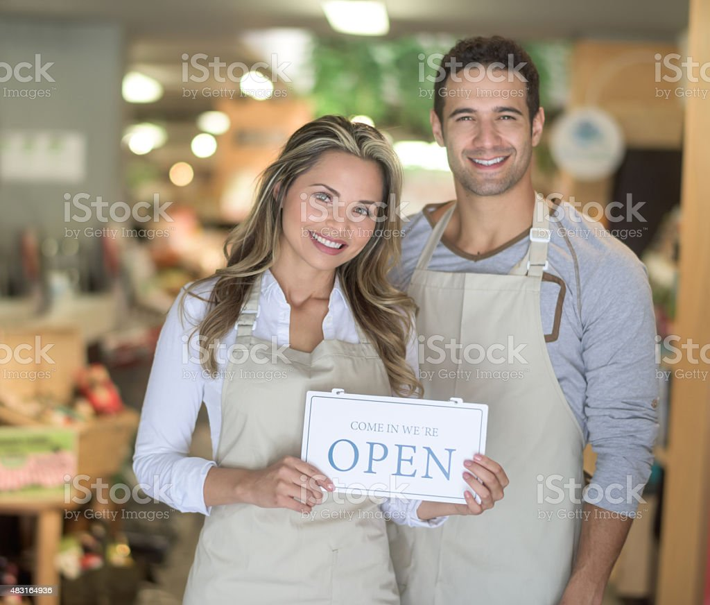 People working at a supermarket and holding an open sign stock photo