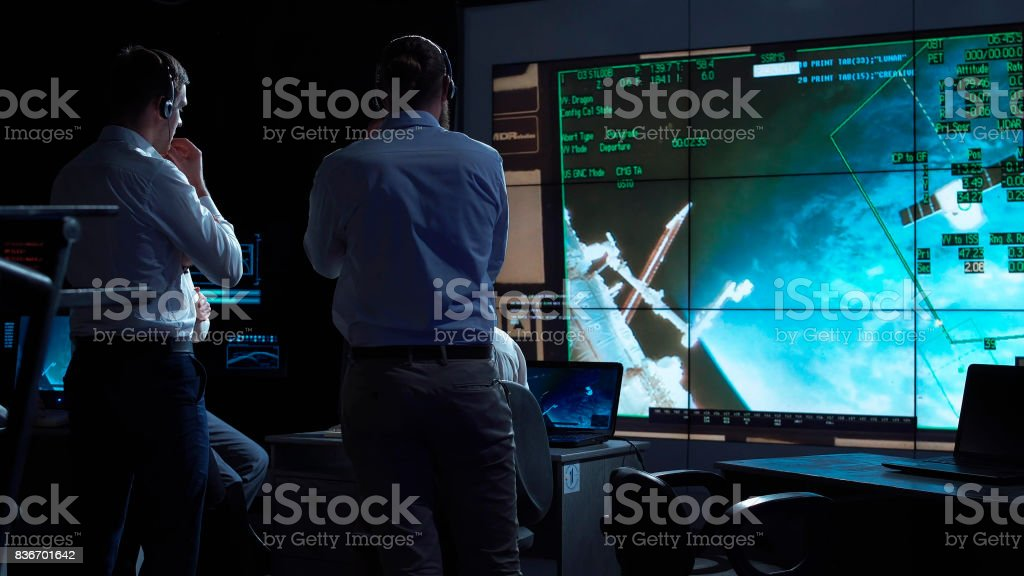 People working in mission control center stock photo