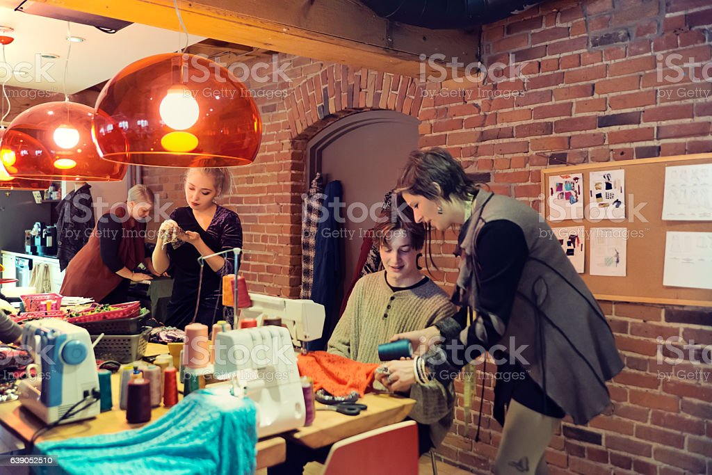 People working in small fashion enterprise lead by woman. stock photo