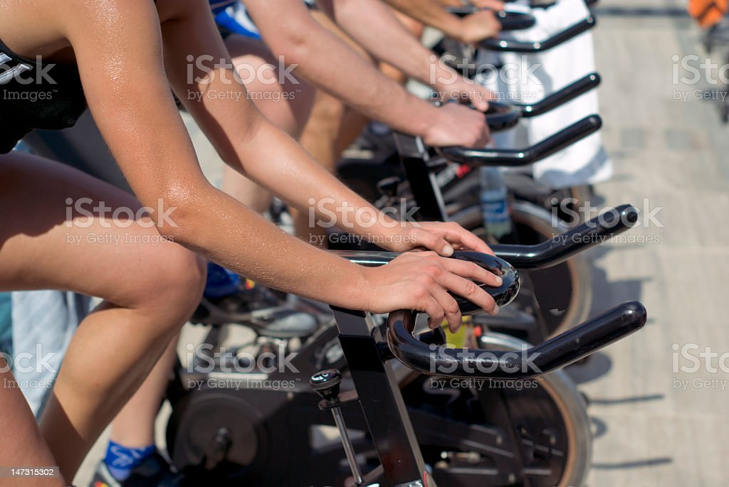 People working out on cycling machines stock photo