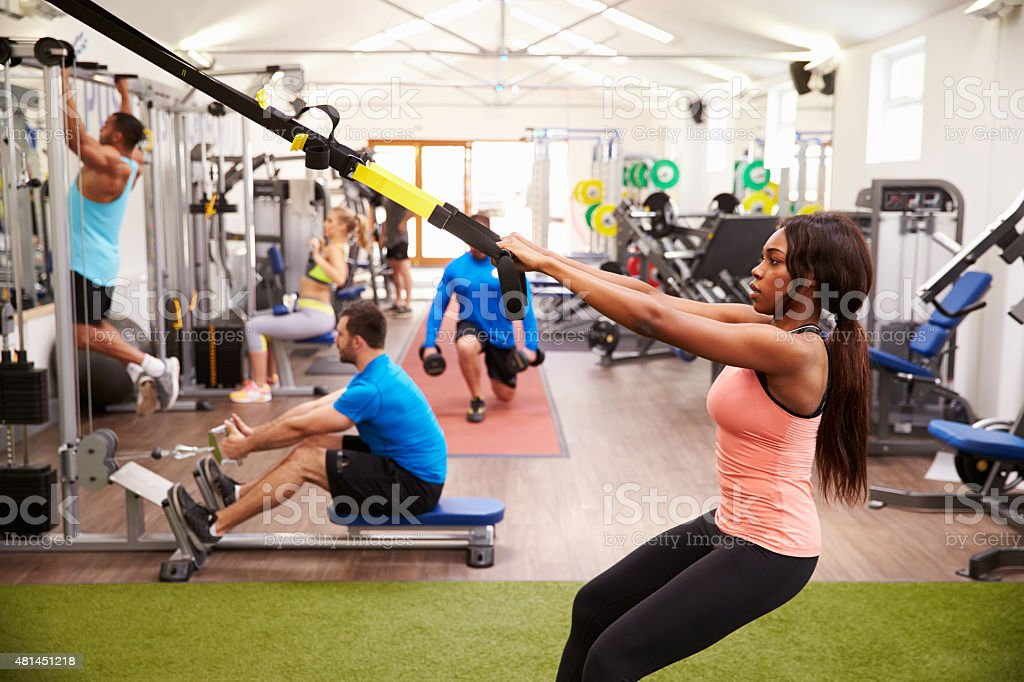 People working out on fitness equipment at a busy gym stock photo