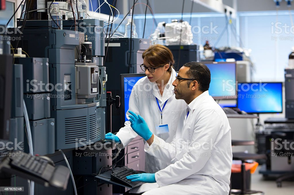 Scientists in a laboratory recording data. Both working beside a...