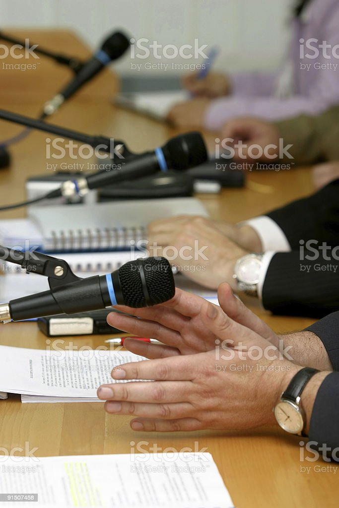 People's hands on a conference table by microphone royalty-free stock photo