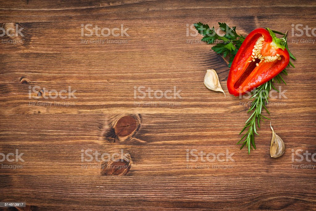 Pepper and garlic in greens on wooden board with copyspace stock photo