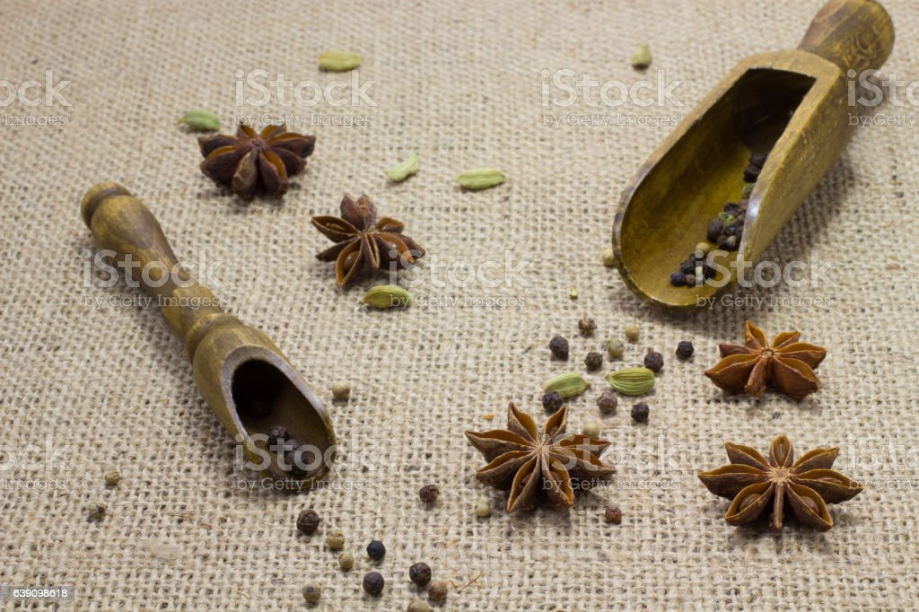 pepper in  wooden spoons, star anise cardamom on a table stock photo