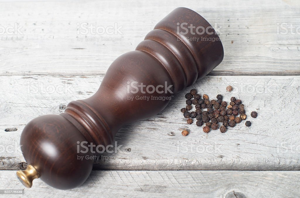 Pepper mill and black peppercorn stock photo