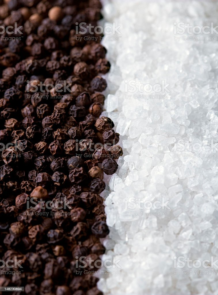 Peppercorns and salt crystals lined up next to each other  stock photo