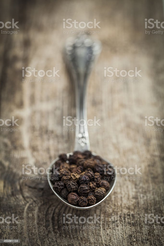 Peppercorns on a spoon over wooden background stock photo