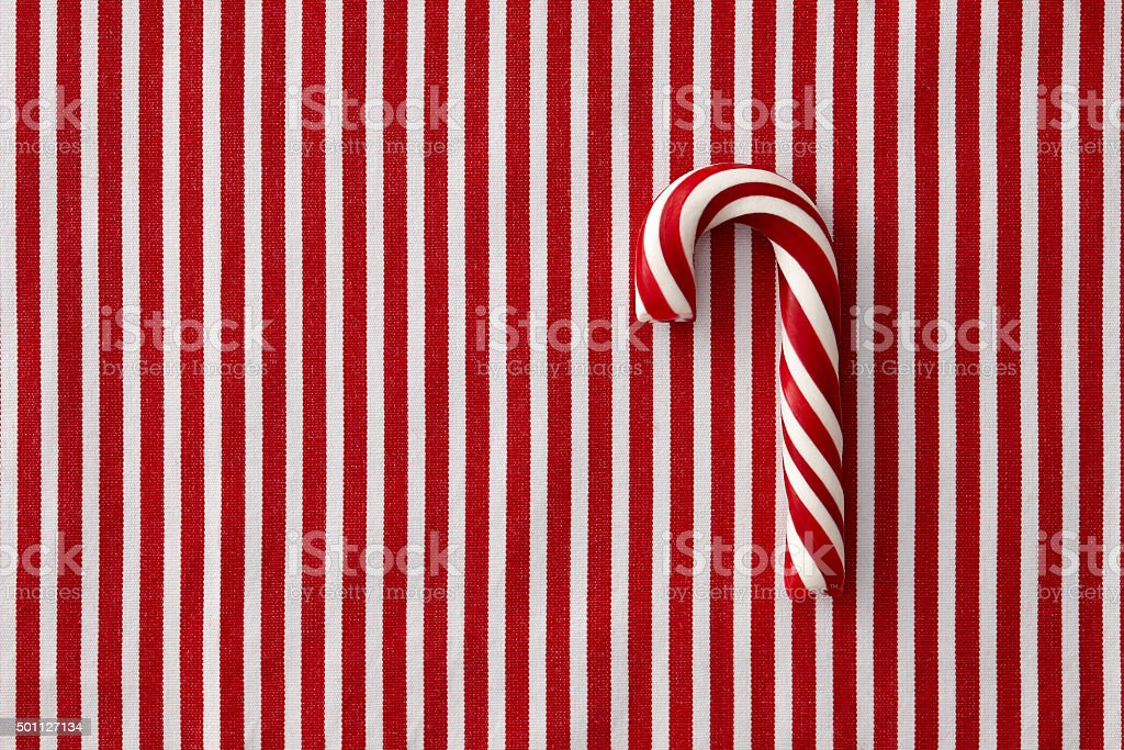 Peppermint candy cane on striped background stock photo