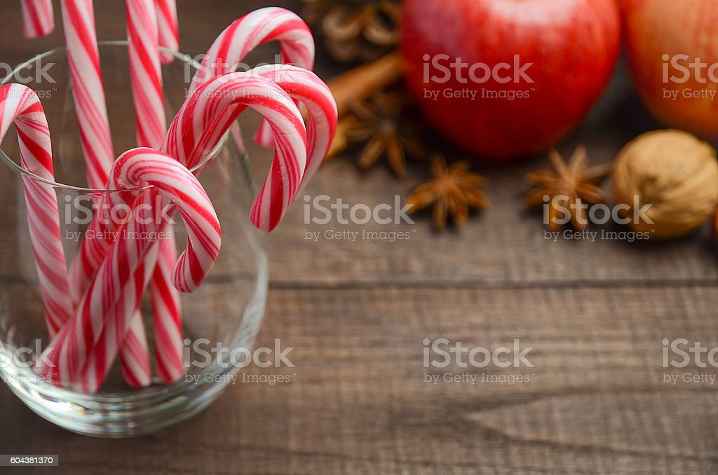 Peppermint Candy Canes and other Christmas decorations on wooden background stock photo