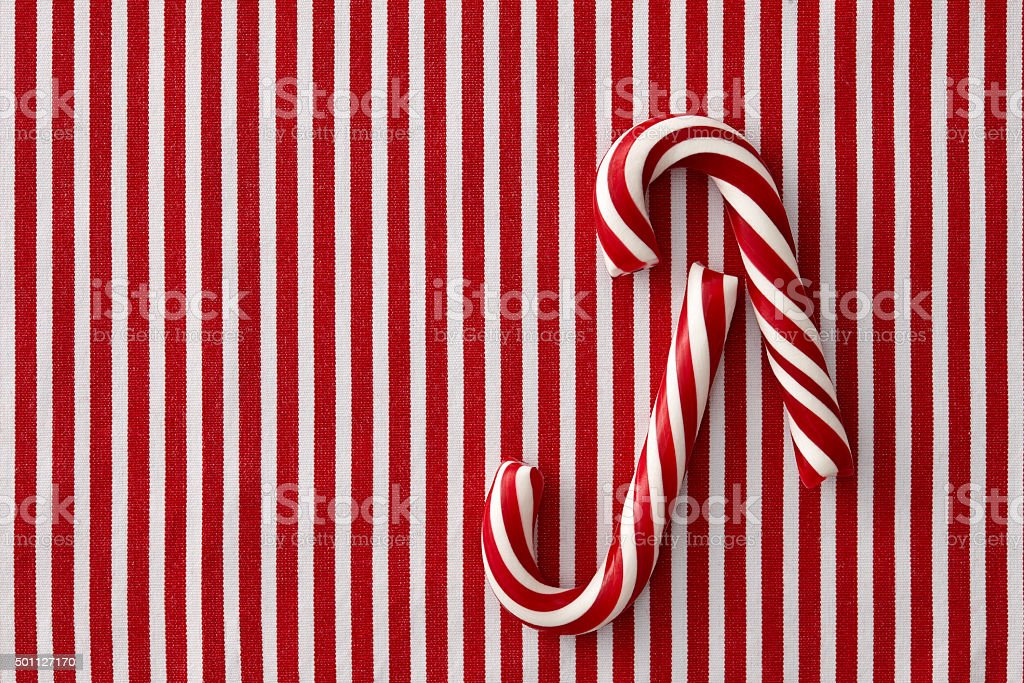 Peppermint candy canes on striped background stock photo