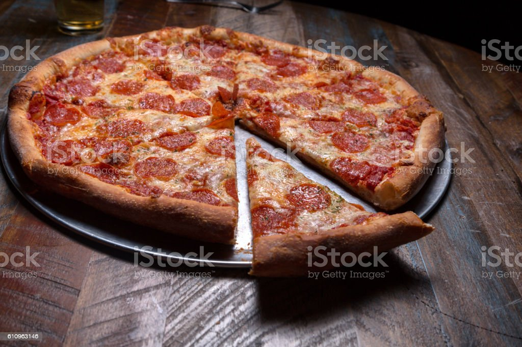 Pepperoni Pizza on a Rustic Table stock photo