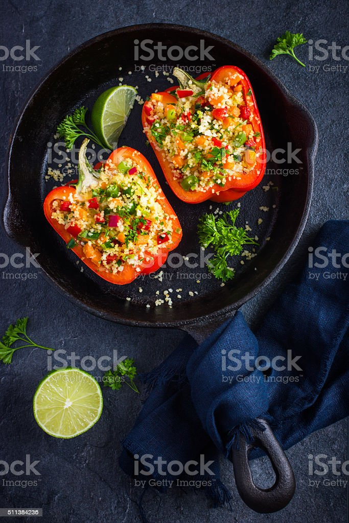peppers staffed with coucous and vegetables on cast iron pan stock photo
