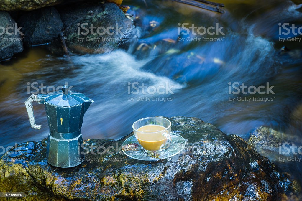 Percolator And hot coffee on a rock stock photo