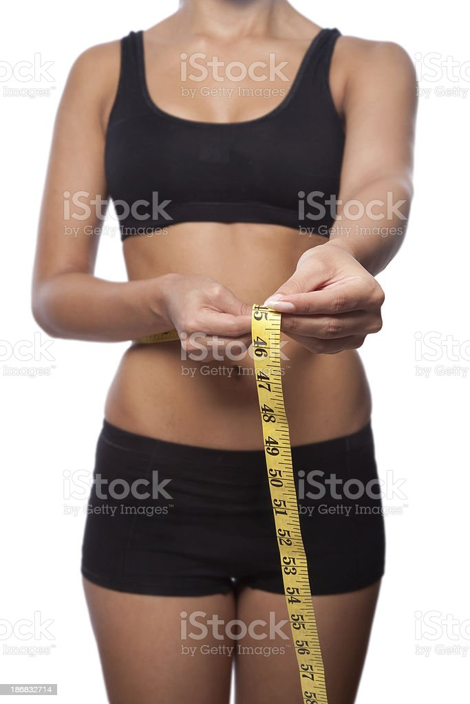 Perfect beautiful woman is measuring her waist royalty-free stock photo