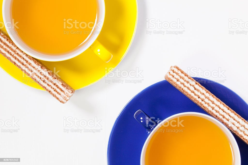Perfect cups of tea on wooden table with sweet wafers stock photo