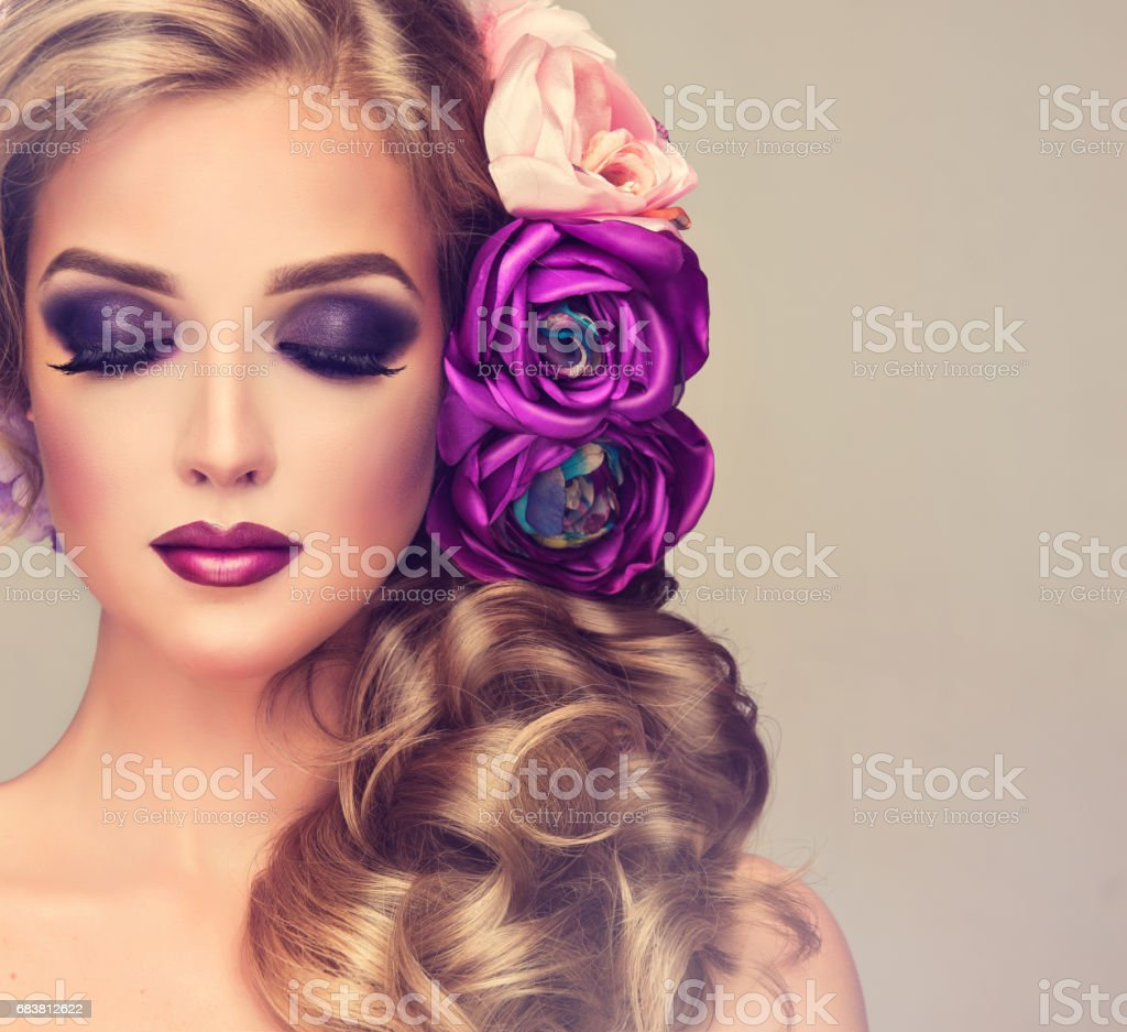 Beautiful model with a big violet and white flowers in her blonde...
