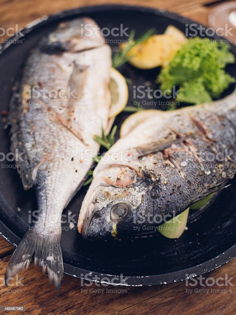 Perfectly grilled whole fish on a dark plate with lemon stock photo
