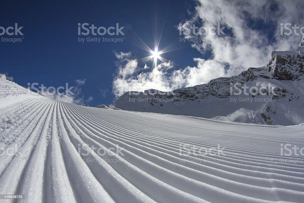 perfectly groomed empty ski piste stock photo