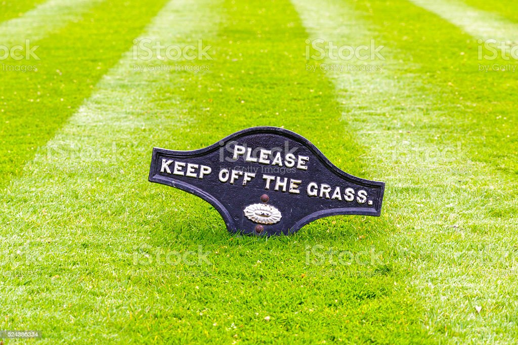 Perfectly striped freshly mowed garden lawn with a warning sign stock photo