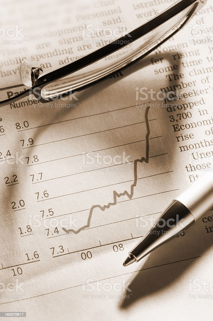 Performance graph in newspaper with pen and glasses royalty-free stock photo