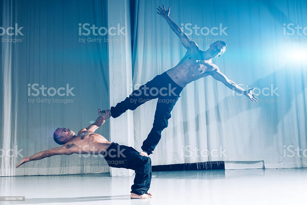 Performance indoor by two strong and muscular acrobats stock photo