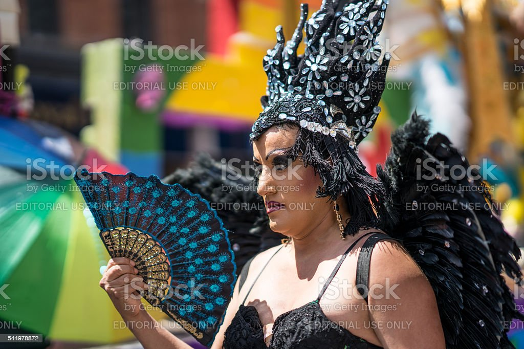 LGBT performer marches in the parade wearing feathers stock photo