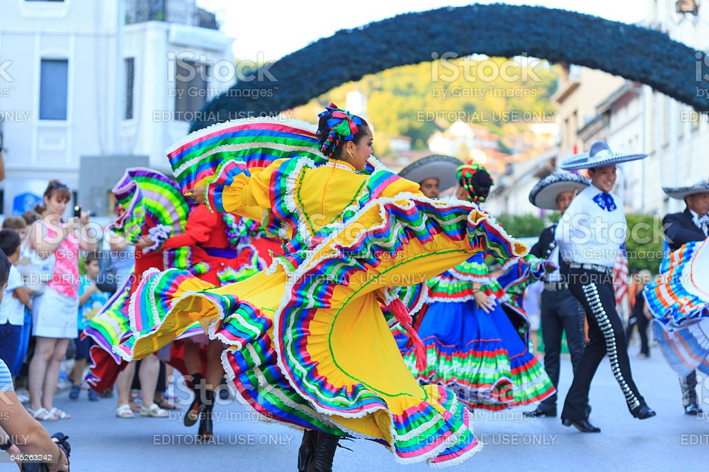 Performers in traditional costumes from Mexican group dancing on street stock photo